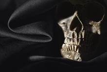Closeup Photo An Old Skull Covered In Black Robe