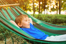 Happy Child Relaxing In Hammock. Summer Vacation Concept. Cute Boy Lying In A Hammock In Garden, Dreaming. Happy And Healthy Childhood