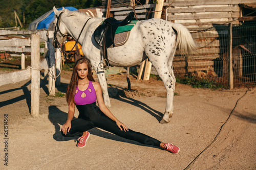Deurstickers Stierenvechten beautiful young woman with dark hair in sportive clothes posing with white horse in stable