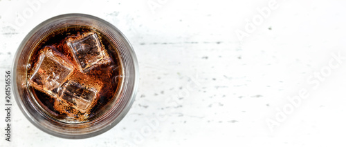 Top down view, glass with cola and ice cubes on white stone board - wide banner, Canvas Print