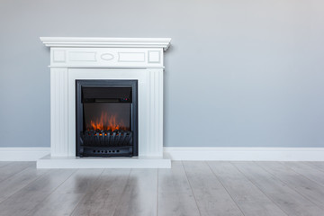 White wooden decorative electric fireplace with a beautiful burning flame. Interior photo on gray background. Place for a simple text.