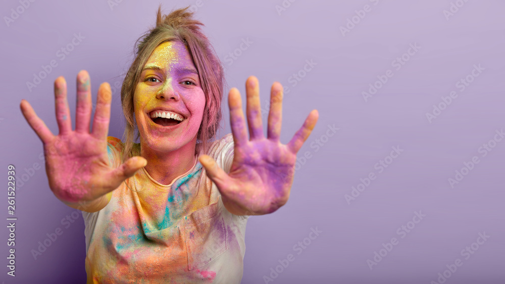 Fototapety, obrazy: Indoor shot of glad positive Caucasian woman shows colorful palms, stretches hands, splashes powder, smiles positively, isolated over purple background with empty space. Holi festival concept
