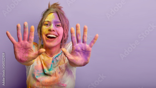 Indoor shot of glad positive Caucasian woman shows colorful palms, stretches hands, splashes powder, smiles positively, isolated over purple background with empty space Fototapet