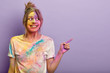 Leinwanddruck Bild - Merry delighted female plays with holi colors, has fun at festival, points away with fore finger, advertises copy space, likes bright colours splatted on face and t shirt, gestures over purple wall