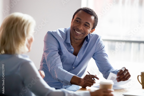 Smiling african american manager talking with client at business meeting Poster Mural XXL