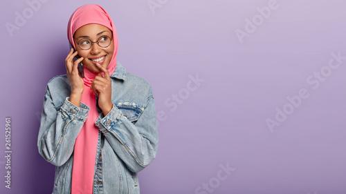 Fotografie, Obraz  Joyful pretty Muslim woman wears pink headwear according to religious dress code