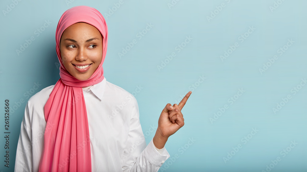 Fototapety, obrazy: Smiling black woman has cheerful expression, points away with fore finger, shows blank space on right corner, has modest look, wrapped in pink veil, isolated over blue background. Look at this