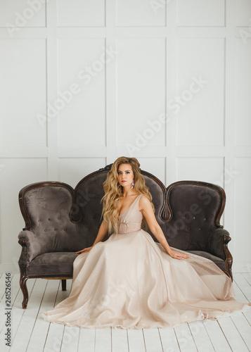 Valokuva  Beautiful blonde woman with greek hairstyle in beige powdery atlas wedding dress posing in studio room