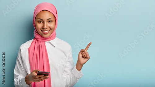 Tablou Canvas Photo of glad Arabic woman with gentle smile on face, points with fore finger on