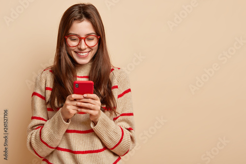 Fotografie, Obraz  Indoor photo of satisfied teenage girl texts on cellular, reads interesting arti
