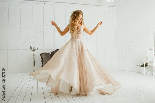 Pinturas sobre lienzo  Beautiful blonde woman with greek hairstyle in beige powdery atlas wedding dress posing in studio room