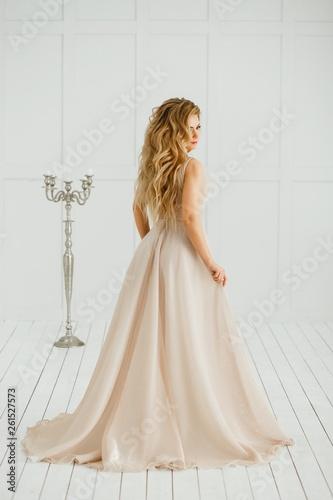 Beautiful blonde woman with greek hairstyle in beige powdery atlas wedding dress posing in studio room Canvas-taulu