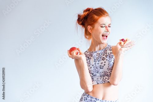 Leinwand Poster Happiness of Cheat meal day for fitness young woman have choosing to eat dessert and say no healthy fruit on her diet plan