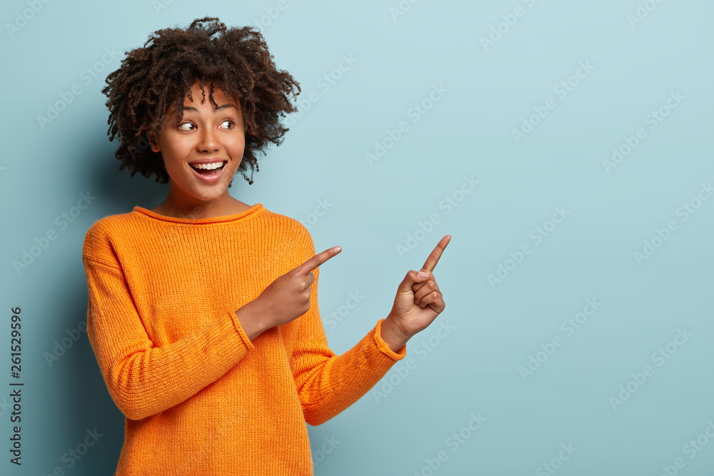 Fototapeta Horizontal shot pleased dark skinned female with Afro haircut, points away with both fore fingers, shows blank space for your promotion, isolated over blue background. People, advertisement concept