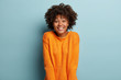 canvas print picture - Joyful Afro American girlfriend gets unexpected surprise from boyfriend, has broad smile, feels pleased, wears orange jumper, expresses nice emotions, isolated over blue background. Facial expressions