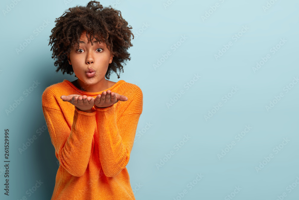 Fototapety, obrazy: Beautiful black girl makes air kiss, blows over two palms, wants to kiss man, has healthy skin, wears orange jumper, poses against blue background with empty space for your promotional content