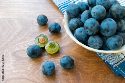 Photo  Bowl full of blackthorn on the wooden table