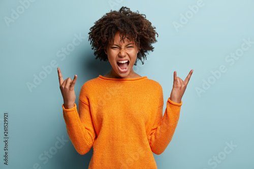Emotional dark skinned female makes rock n roll gesture, enjoys cool music at party, frowns face, opens mouth, demonstrates hand gesture, dressed in orange jumper, models over blue background - 261529921