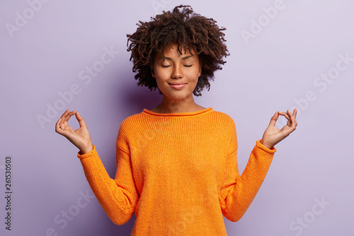 Pleasant looking calm woman meditates indoor, holds hands in mudra gesture, has charming smile, closed eyes, wears orange clothes, models over purple background. Hand gesture. Meditation concept