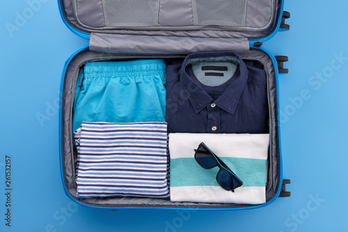 Stampa su Tela Travel suitcase with clothes on blue background