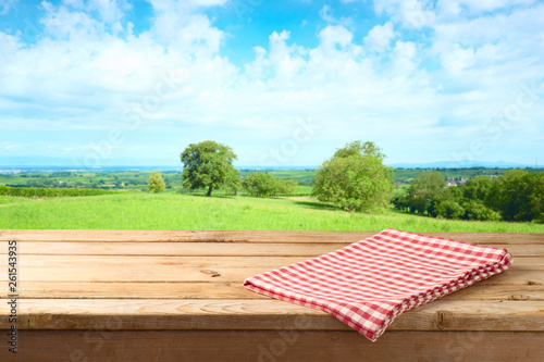 Obraz Empty wooden table with tablecloth over summer meadow background - fototapety do salonu