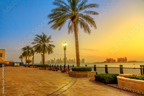 Fényképezés  Benches and palm trees along marina walkway in Porto Arabia at the Pearl-Qatar, Doha, with skyscrapers of West Bay skyline illuminated at blue hour