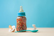 canvas print picture - Baby bottle with multicolored sugar dragee on blue background