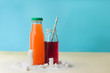 Glass bottles with orange and cherry juice near sugar