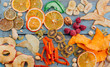 canvas print picture - Dried fruit and vegetable chips, candied pumpkin slices, nuts and seeds on blue wooden background