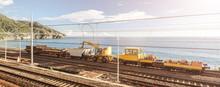 A Train With Heavy Duty Machinery On Italian Railroad Going Along The Coast Near Cinque Terre , Liguria Italy Europe.