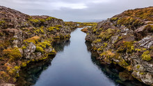 Þingvellir National Park In Iceland, A Place Where Two Tectonic Plates Meet Underwater, The Eurasian Tectonic Plate And The North American Tectonic Plate. A Narrow Water Tunnel Surrounded By Hills.