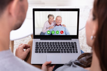 Couple Video Conferencing With Their Parents On Laptop