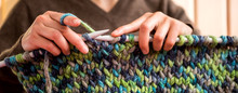 A Woman Knits From Thick Yarn.