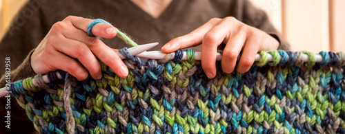 A woman knits from thick yarn. Canvas Print