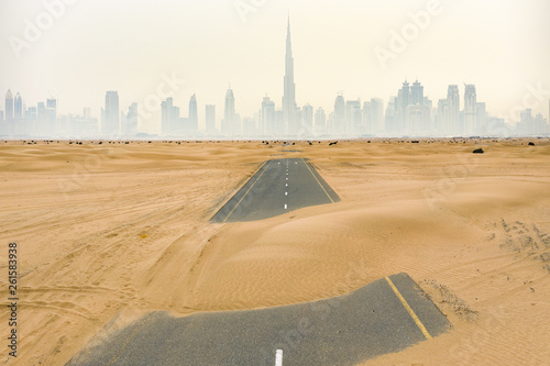 Aerial view of a deserted road covered by sand dunes in the middle of the Dubai desert Fototapeta