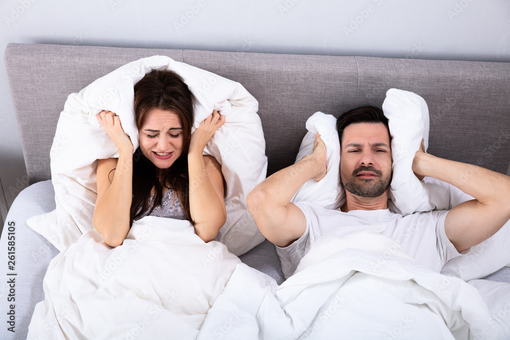 Fototapeta Couple Covering Their Ears With Pillow On Bed