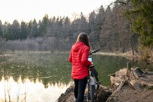 Young Woman With A Bicycle In A Red Jacket Stands On The Shore Of A Forest Lake. Riding A Bike In The Autumn-spring Period. Outdoor Activity