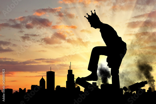 Fotografía Big selfish man with a crown destroys the city on his way