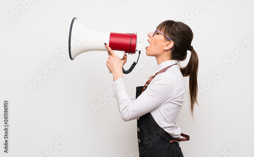 Fotografering Young woman with apron shouting through a megaphone