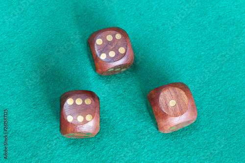 three wooden dices on green baize table Wallpaper Mural