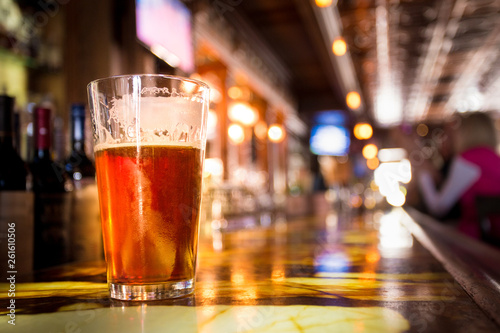 Glass Pint of amber beer with colorful blur of bar in background Wallpaper Mural