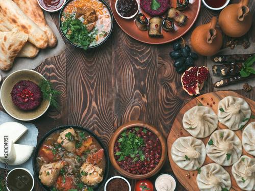 Fototapeta View from above of georgian cuisine on brown wooden table.Traditional georgian food-khinkali,kharcho,chahokhbili,phali,lobio and local sauces - tkemali, satsebeli, adzhika.Top view.Copy space for text obraz