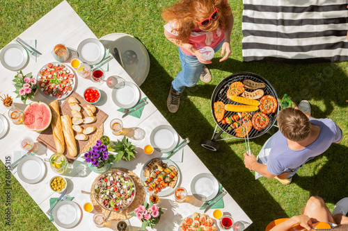 Photo Stands Grill / Barbecue High angle on table with food next to people grilling shashliks during barbecue party