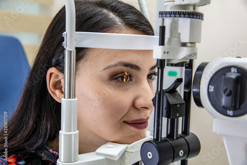 Cuadros en Lienzo High technology concept health for eyes care - The optician ophthalmology doctor optometrist in the eyes clinic using a binocular slit-lamp to a young woman for an eye control