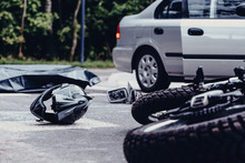 Motorcycle Helmet On The Street After Terrible Car Crash, Black Bag With Corpse And Car With Open Door Next To It
