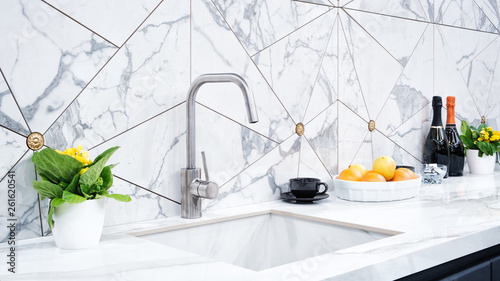 The interior of the modern kitchen is illuminated with a gray stone countertop with a luxury washbasin and mixer, fruit orange and flowers, a bottle with red wine, champagne and chocolate - fototapety na wymiar