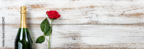 Photo  Anniversary background with red rose and champagne on white weathered wood