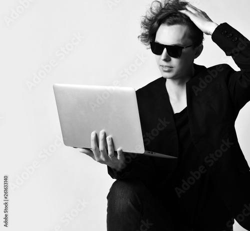 Valokuva  Young modern man in sunglasses looks at  something on laptop that holds on his knee and scratches his head thoughtfully