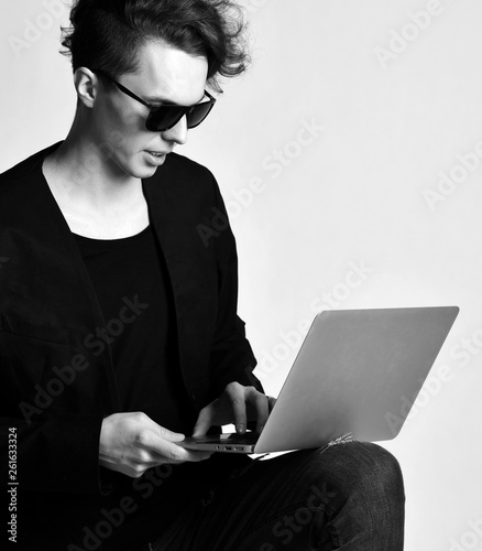 Photo  Young modern man in jeans black jacket suit and sunglasses work on laptop comput