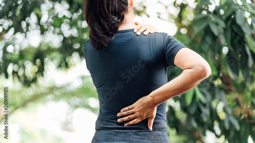 Cuadros en Lienzo  young asian woman hurts her back and neck, Ache in human body , office syndrome